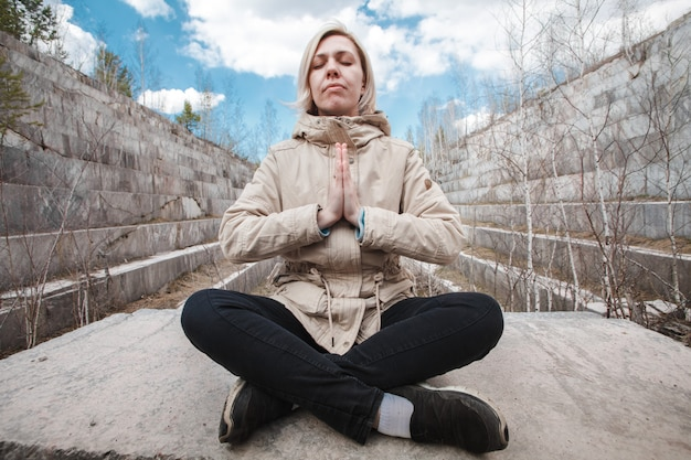 Portrait of a meditating blonde outdoors