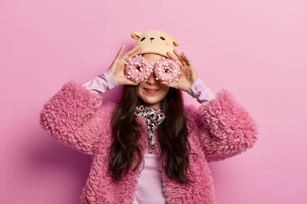 Ritratto di donna allegra copre gli occhi con gustose ciambelle, riceve molte calorie, si veste con abiti invernali alla moda, mangia cibo spazzatura, gioca con i dolciumi