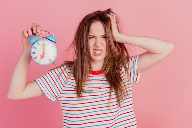 Portrait of messy hairstyle mad lady hold alarm clock timer tear hair on pink background