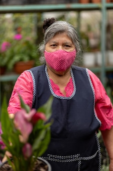Portrait of a mexican woman  in nursery xochimilco, mexico wearing face mask
