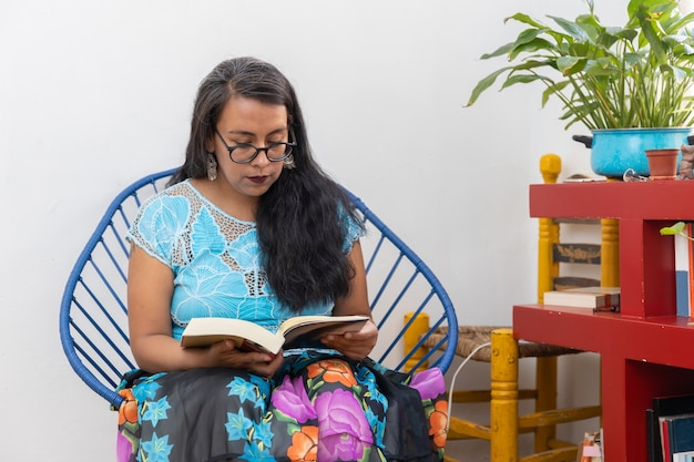 Portrait of a mexican young woman wearing tehuana clothes, reading and studying