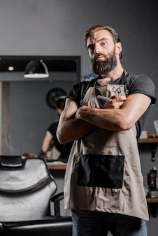 Portrait of a mid adult bearded male barber with folded arms