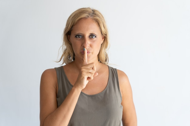 Portrait of mid adult blond-haired woman showing silence gesture.