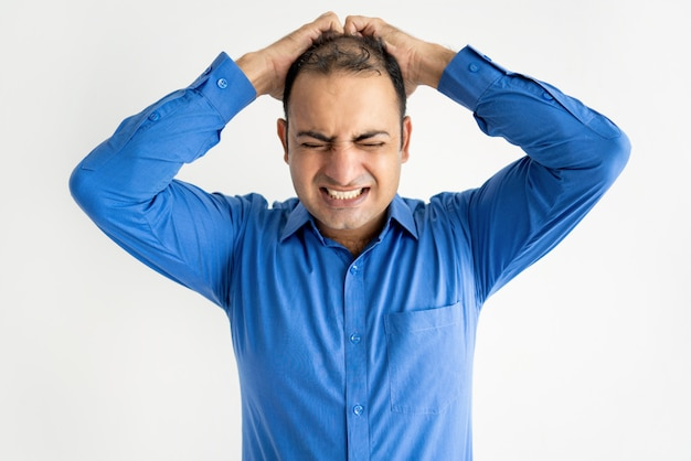 Portrait of mid adult businessman crying holding head in hands