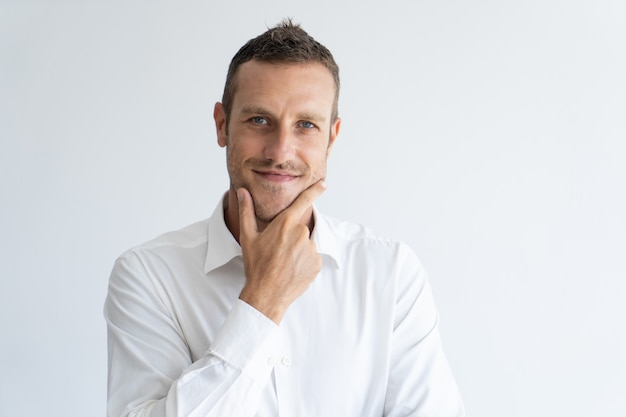 Portrait of mid adult businessman with interested expression touching his chin