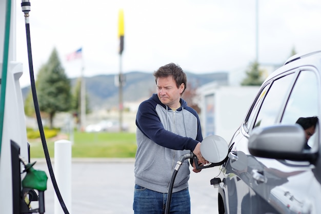 Portrait of middle age man filling gasoline fuel in car