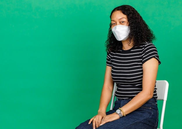 Portrait of middle aged asian woman wearing mask sitting down on chair on green background. concept for covid 19 vaccination.