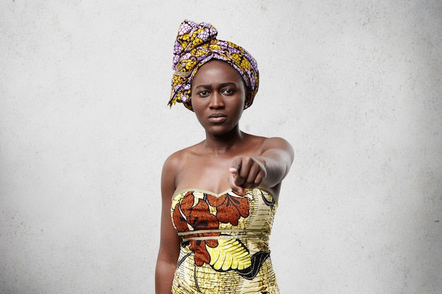 Portrait of middle-aged black woman with slender figure wearing scarf on head and beautiful dress standing against white concrete wall pointing at you with forefinger having serious expression