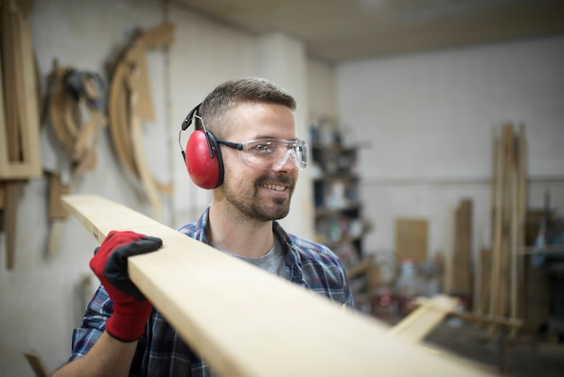 Portrait of middle aged blonde carpenter with eyes and ears protection carrying wooden plank in woodworking carpentry workshop