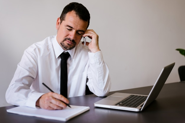 Portrait of middle aged businessman talking on mobile phone in office