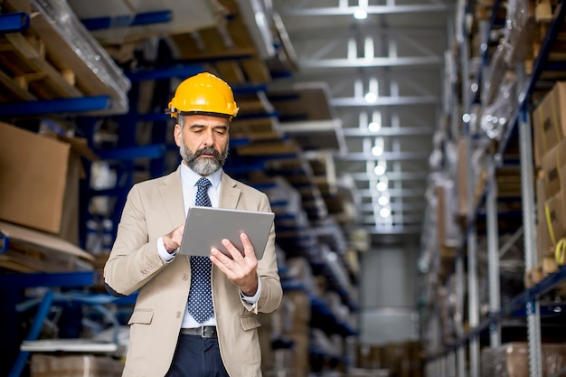 Portrait of middle-aged businessman with digital tablet in factory