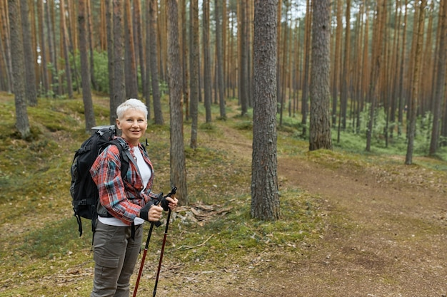 Portrait of middle aged female in activwear standing on trail in national park using poles for nordic walking