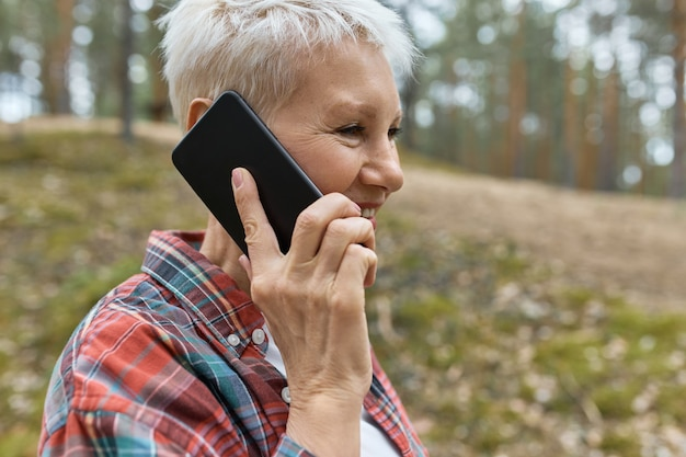 Portrait of middle aged female with wrikles posing outdoors in plaid shirt holding smart phone at her ear, having nice conversation, enjoying walk in forest.