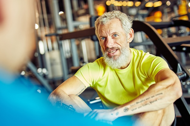 Portrait of a middle aged man discussing training plan with fitness instructor or personal trainer