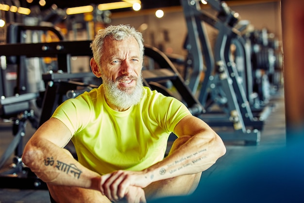Portrait of a middle aged man discussing workout plan with fitness instructor while sitting