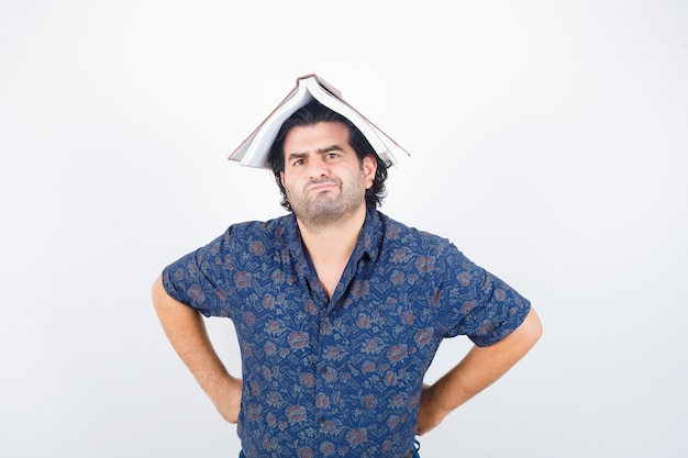 Portrait of middle aged man holding book on head as house roof in shirt and looking hesitant front view