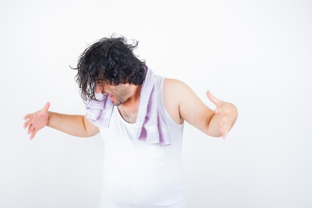 Portrait of middle aged man keeping hands in aggressive manner in tank top, towel and looking angry front view