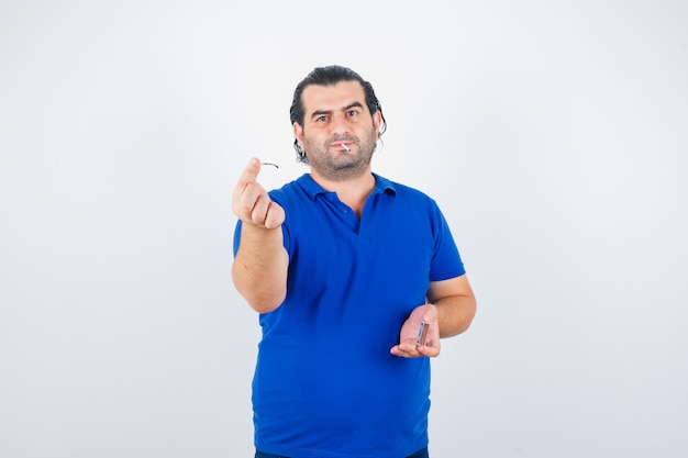 Portrait of middle aged man lighting matches in polo t-shirt and looking pensive front view
