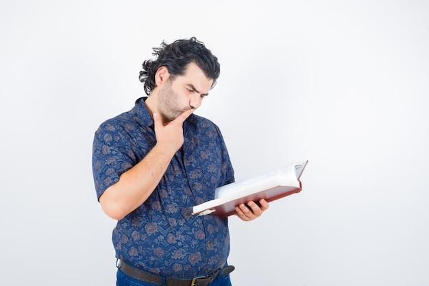 Ritratto di uomo di mezza età guardando il libro in camicia e guardando premurosa vista frontale