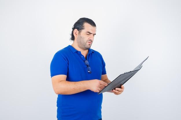 Ritratto di uomo di mezza età guardando attraverso appunti in t-shirt polo e guardando premurosa vista frontale
