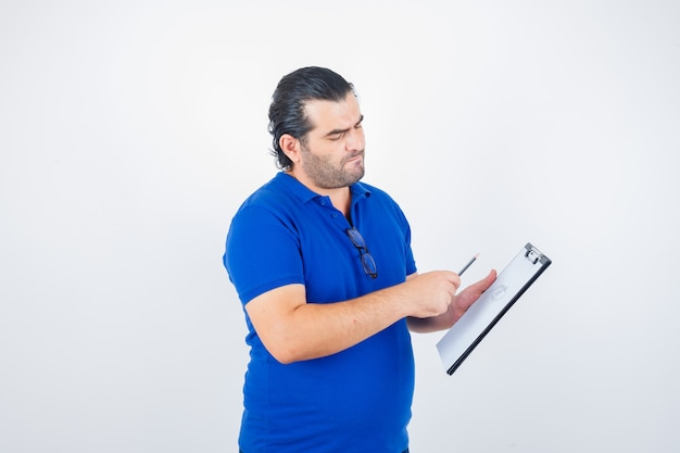 Portrait of middle aged man looking through clipboard while holding pencil in polo t-shirt and looking pensive front view