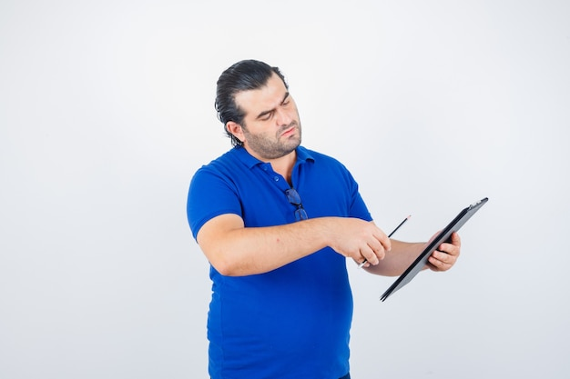 Portrait of middle aged man looking through clipboard while holding pencil in polo t-shirt and looking thoughtful front view