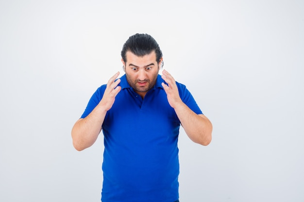Portrait of middle aged man raising hands over chest in blue t-shirt and looking puzzled front view