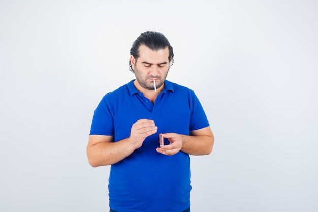 Portrait of middle aged man trying to light cigarette with matches in polo t-shirt and looking focused front view