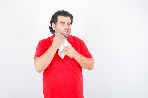 Ritratto di uomo di mezza età asciugandosi la guancia con un tovagliolo in maglietta rossa e guardando premurosa vista frontale