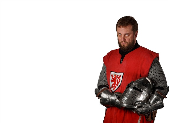 Portrait of a middle-aged man with a beard in the clothes and armor of a medieval knight with a helmet in his hands isolated on a white wall