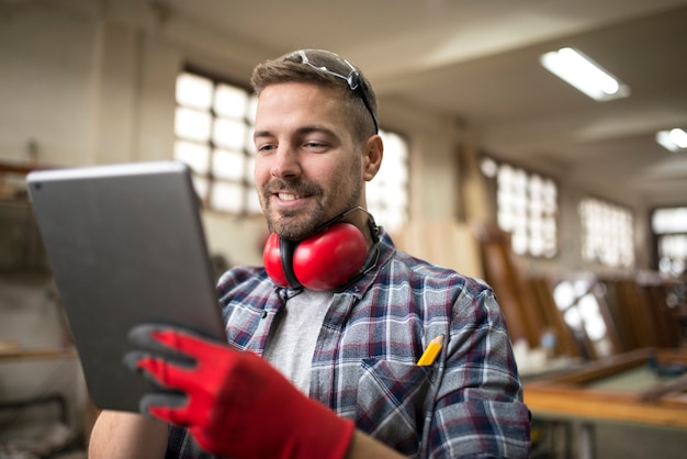 Portrait of middle aged professional worker carpenter with ear protectors using tablet in carpentry workshop