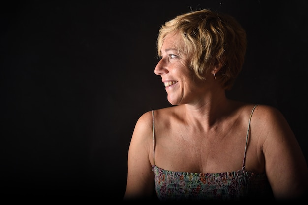 Portrait of a middle aged woman on black