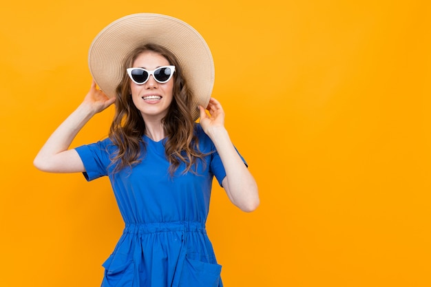 Portrait of a middle-aged woman in a blue dress on a background of a yellow wall, a girl in sunglasses with a smile