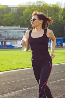 Portrait of middle aged woman running with bottle of water in the stadium