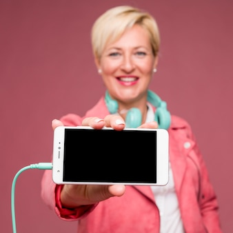 Portrait of middle aged woman showing smartphone template