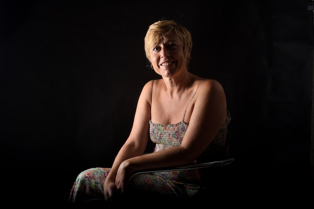 Portrait of middle aged woman sitting on a chair on black