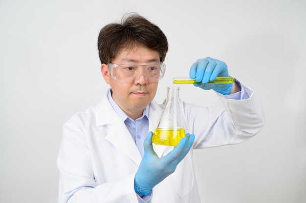 Portrait of a middle-year asian male scientist wearing a white lab gown and gloves and holding an experimental container in his hand.