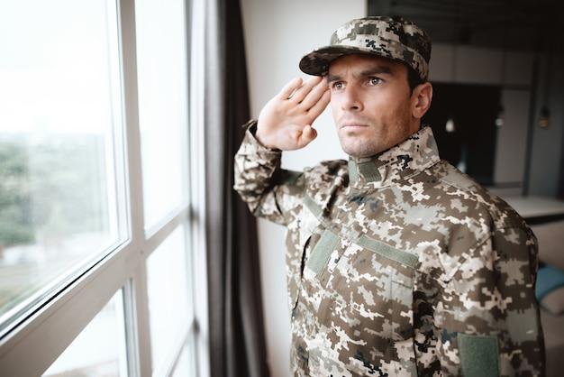 Portrait of military uniform salute near window.