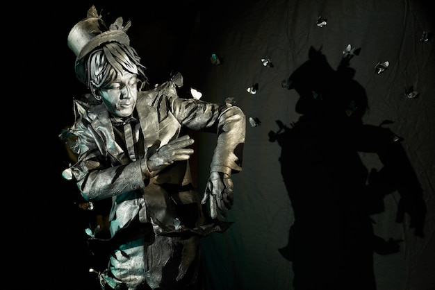 Portrait of mime artist whose hair, face, suit and hands are totally painted,playing with a lot of unreal butterflies flying around. male pantomime actor performing art on black background