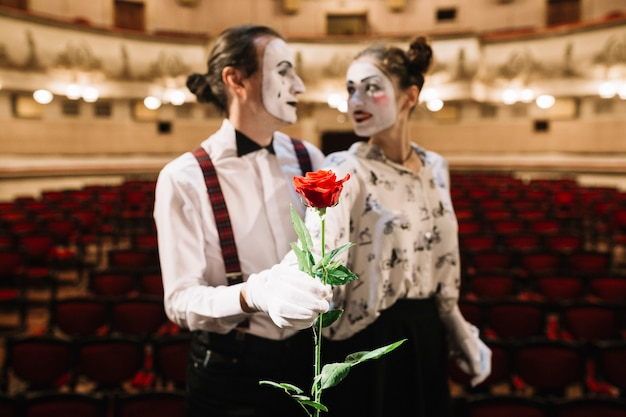 Portrait of mime couple holding red rose in the auditorium