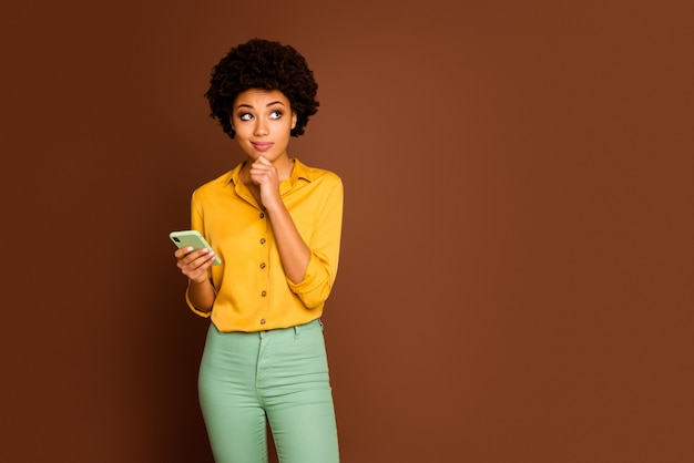 Portrait of minded creative afro american girl use cellphone want post blog comment think dreamy look copy space touch chin hands wear yellow green trousers isolated brown color