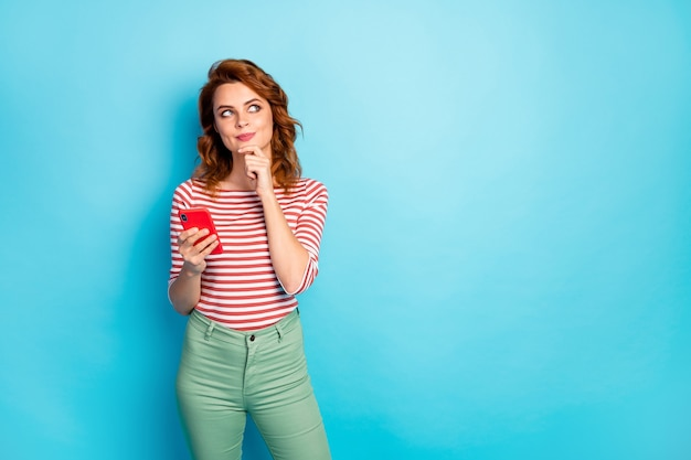 Portrait of minded inspired girl addicted social media user use cellphone think thoughts post comment wear stylish pullover isolated over blue color Premium Photo