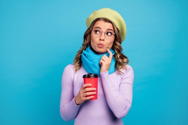 Портрет настроенная заинтересованная девушка держит чашку напитка думает, мысли на синей стене