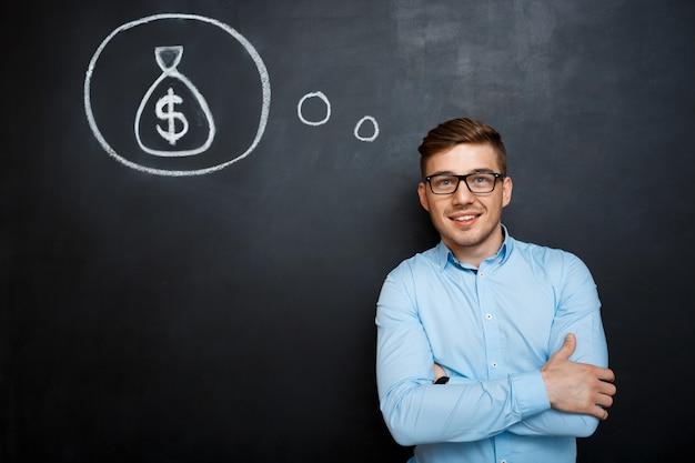 Portrait of minded man crossed hands over blackboard money conc