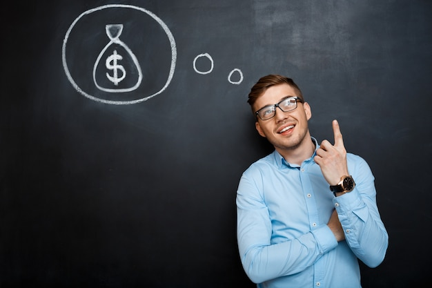Portrait of minded man pointing on his mind about money