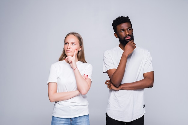 Portrait of mixed race couple thinking and looking worried about their relationship iolated on white wall