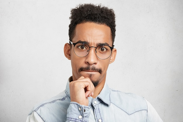 Portrait of mixed race serious focused bearded man with afro hairstyle, keeps hand on chin, pressses lips,