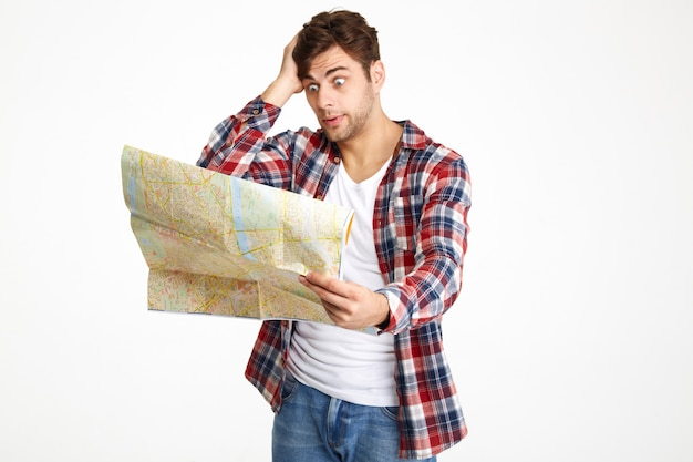 Portrait of a mixed-up young man looking at travel map
