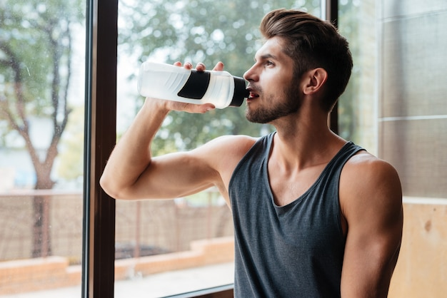 Portrait of model in gym with bottle