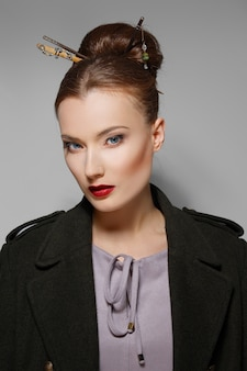 Portrait of model with oriental hairstyle, red lips and blue eyes. perfect healthy skin.